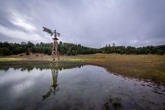 Een eenzame, doorstane windmolen bevindt zich lang stock fotografie