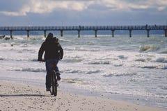Een eenzame fietser in donkere kleren berijdt op een zandig strand naar de pijler Royalty-vrije Stock Foto