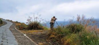 Een eenzame fotograaf die foto's in regenachtig weer bij de terrasvormige padievelden van Longsheng, Guilin, Guangxi, China doen royalty-vrije stock afbeelding