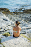 Een eenzame jonge vrouw in een bikini zit op de rotsachtige kust, lettend op het overzees royalty-vrije stock afbeeldingen