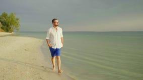 Een eenzame mens in lichte kleren loopt blootvoets langs het zand langs het overzees Vlucht van zorgen, vrijheid en verlof 4K lan stock video