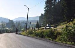 Een eenzame mens met een hond loopt langs wegen Royalty-vrije Stock Foto's