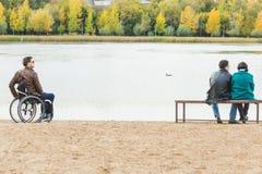 Een eenzame mens in een rolstoel en een paar op een parkbank royalty-vrije stock afbeeldingen
