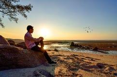 Een eenzame mensenzitting op de rots Stock Foto