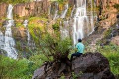 Een Eenzame Mensenzitting op Rotsen en het Bekijken een Majestueuze Draperende Waterval royalty-vrije stock fotografie