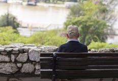 Een eenzame oude mensenzitting op een bank in een park, die rivier bekijken royalty-vrije stock fotografie