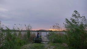 Een eenzame schilder in een boot bij zonsondergang stock video