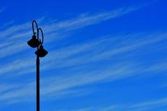 Een eenzame straatlantaarn in een blauwe hemel Stock Foto