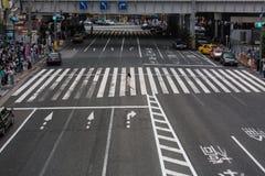 Een eenzame vrouwenlooppas over een bezige kruising in Tokyo, Japan Royalty-vrije Stock Foto's