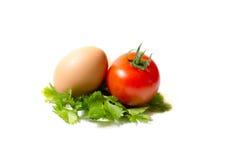 Een ei en een tomaat op een blad van Parshley Stock Foto's