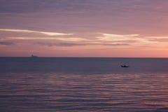 Een eilandbewoner paddelt een uitgegraven kano bij zonsondergang stock afbeelding