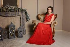 Een elegant donkerbruin meisje in een rode kleding zit als voorzitter in het binnenland van een fabelachtig Nieuwjaar stock afbeelding