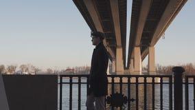 Een elegant geklede mens loopt langs de dijk langs de rivier in de de lenteavond stock videobeelden
