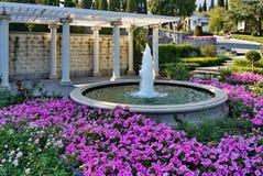 Een elegante blik van een mooi bloembed met roze bloemen die rond een fontein van afstraffing in een concrete kom op a groeien stock fotografie