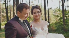Een elegante bruidegom en een charmante bruid met een helder boeket, die langs een bossleep onder de pijnbomen lopen Gelukkig stock video