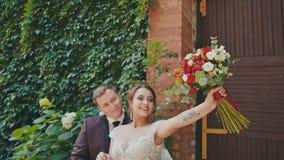 Een elegante bruidegom en een mooie bruid met een helder boeket op de achtergrond van een bakstenen muur met het kweken van takke stock video