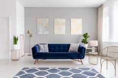 Een elegante marineblauwe bank in het midden van een helder woonkamerbinnenland met gouden metaal zijlijsten en drie schilderijen stock afbeeldingen