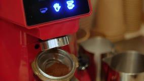 Een elektrische koffiemolen maalt vers geroosterde koffiebonen in een filterhouder stock video