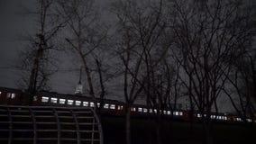 Een elektrische trein gaat door de post over bij nacht stock footage