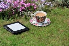 Een elektronische boeklezer en een kop van koffie op het gras Stock Afbeeldingen