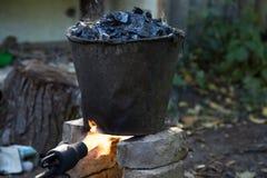 Een emmer teer op de brand, voor dakreparaties stock afbeeldingen