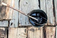 Een emmer zwarte teer kookt op de brand voor gebruik in reparatie en het waterdicht maken stock afbeelding