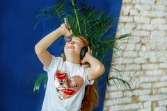 Een emotioneel kind luistert aan muziek en zingt Het concept is CH Royalty-vrije Stock Afbeelding