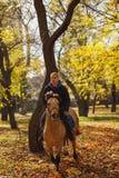 Een emotionele kerel, berijdt een mooi paard met een bang gemaakte blik In het de herfstpark stock fotografie