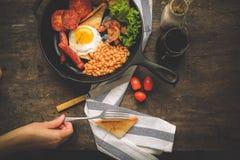 Een Engels ontbijt is een ontbijtmaaltijd die typisch bacon, worsten, eieren omvat stock foto's