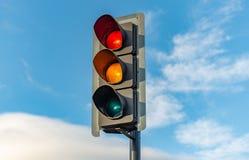 Een Engels verkeerslicht zit tegen een heldere blauwe hemel stock foto