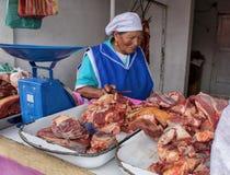 Een equatorian vrouw verkoopt vers rundvleesvlees op de markt Quito, Ecuador stock fotografie