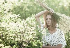 Een ernstig meisje in een strohoed beschermt haar gezicht met een bos van onkruid hoog gras, stock foto's