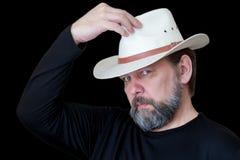 Een ernstige gebaarde mens op middelbare leeftijd zet op een cowboyhoed stock afbeeldingen