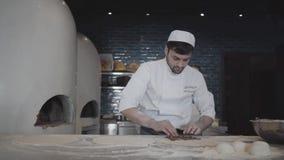Een ervaren chef-kok in witte eenvormig bereidt een heerlijke kebab voor De kok zet het vullen in het deeg stock video