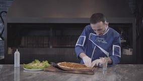 Een ervaren chef-kok in witte eenvormig bereidt een heerlijke khachapuri voor De kok zet het vullen in het deeg stock videobeelden