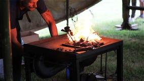 Een ervaren smid verwarmt omhoog het metaal en smeedt gesmolten metaal op het aambeeld in de smidse stock footage