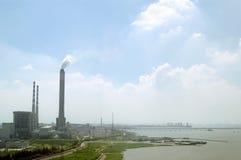 Een fabriek door de rivier stock afbeeldingen