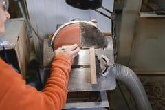 Een fabrieksarbeider, scherpt houten kleine bars voor speciaal materiaal royalty-vrije stock fotografie