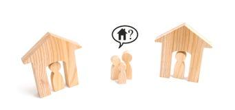 Een familie bevindt zich tussen twee gewoonde in huizen Het concept gebrek aan huisvesting Dure huisvesting en leningen Dakloze f stock afbeeldingen