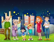 Een familie bij de stad die zich voor de lange gebouwen bevinden Stock Foto's