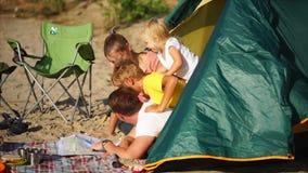 Een familie die besteedt gelukkige dagen op het strand bekijkt de kaart, worden de kinderen voor de gek gehouden stock videobeelden