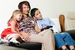 Een familie die op een TV let Stock Afbeeldingen