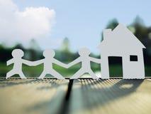 Een familie en een huis in het park, sparen geld voor toekomstig onroerende goederenconcept royalty-vrije stock afbeeldingen