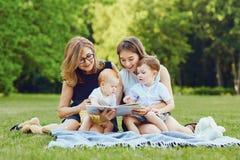 Een familie leest een boek op het gras royalty-vrije stock foto