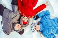 Een familie met een kind die in de sneeuw liggen royalty-vrije stock afbeelding