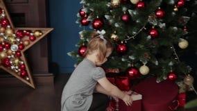 Een familie van drie opent de giften van het Nieuwjaar dichtbij de open haard, Kerstmis 2019 stock video