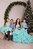 Een familie van vier met een jongen en een meisje in elegante kostuums en kleding zitten bij een banket dichtbij de Nieuwjaarboom stock afbeeldingen