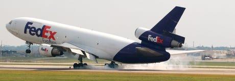 Een Fedex-Vliegtuigaanrakingen neer bij de luchthaven Stock Foto