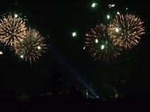 Een feestelijke begroeting in de donkere avondhemel wordt verlicht van de grond door de stralen van licht voor nog groter effect Stock Fotografie
