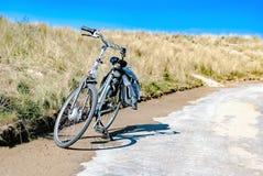 Een fiets langs een kustweg met duinen bij de achtergrond wordt geparkeerd die Het concept van de zomer Vakantie Fietshuur biking stock afbeelding